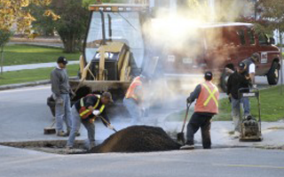 Image of men and machinery performing repair of pothole