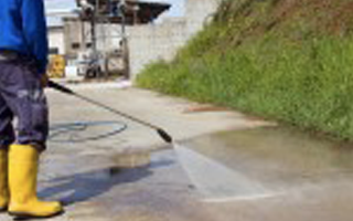 Image of worker pressure washing a job site