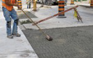 Image of worker smoothing recently poured concrete